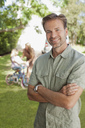 Portrait of smiling man with family in background - CAIF00038
