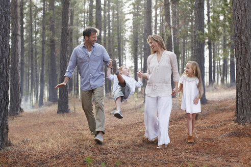 Happy family holding hands and walking in woods - CAIF00056