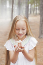 Close up of girl holding butterfly in woods - CAIF00059