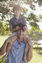 Father carrying smiling son on shoulders at lakeside - CAIF00083