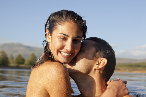 Close up portrait of couple kissing in lake - CAIF00089