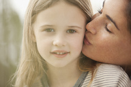 Close up portrait of mother kissing daughter's cheek - CAIF00092