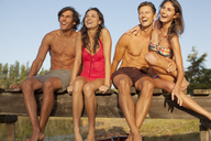 Smiling couples sitting at edge of dock - CAIF00098