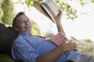 Portrait of smiling man laying on grass with book and hat - CAIF00113