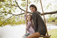Portrait of mother and daughter on swing at lakeside - CAIF00137