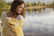 Smiling woman wrapped in blanket at lakeside - CAIF00140