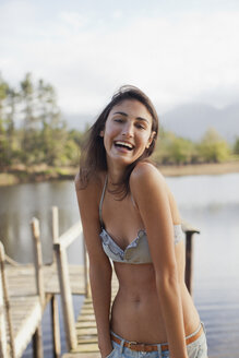 Portrait of enthusiastic woman in bikini at lakeside - CAIF00167