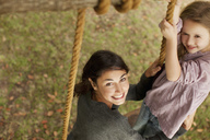 Portrait of smiling mother and daughter on swing - CAIF00176