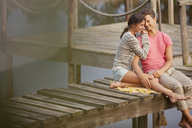 Affectionate couple sitting on dock over lake - CAIF00182