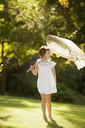 Girl carrying butterfly net in grass - CAIF00185