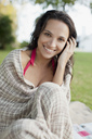 Close up portrait of smiling woman wrapped in blanket - CAIF00197