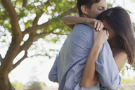 Couple hugging under tree - CAIF00200