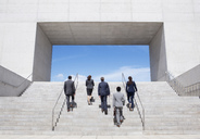Business people ascending modern stairs - CAIF00206