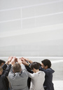 Business people with arms raised in huddle - CAIF00212