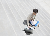 Businesswoman with paperwork using laptop on urban steps - CAIF00215