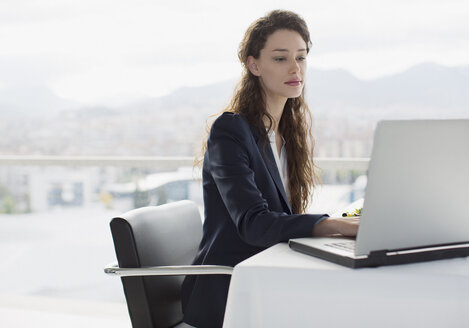 Businesswoman using laptop in office - CAIF00218