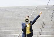 Businesswoman using megaphone on urban steps - CAIF00224