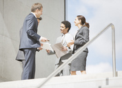 Business people with paperwork meeting at top of stairs - CAIF00248