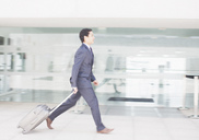 Businessman with suitcase rushing along airport corridor - CAIF00251