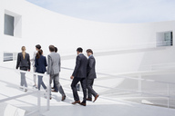 Business people walking up elevated walkway - CAIF00266