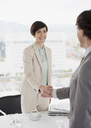 Businessman and businesswoman shaking hands across table - CAIF00293