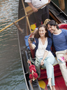 Smiling couple taking photographs in gondola on canal in Venice - CAIF00317
