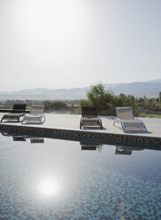 Sun shining over lounge chairs and swimming pool - CAIF00389