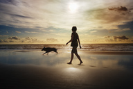Silhouette of woman and dog walking on beach - CAIF00444