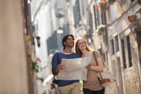 Smiling couple with map on narrow street in Venice - CAIF00459