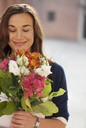 Smiling woman smelling bouquet of flowers - CAIF00465