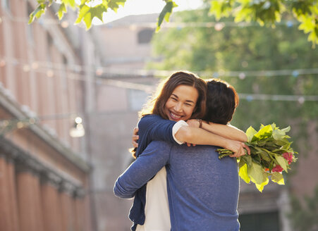 Smiling woman with flowers hugging man - CAIF00474