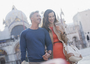 Smiling couple holding hands and walking through St. Mark's Square in Venice - CAIF00477