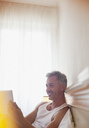 Smiling man using digital tablet in bed - CAIF00480