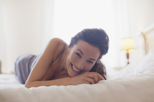 Portrait of smiling woman laying in bed - CAIF00492