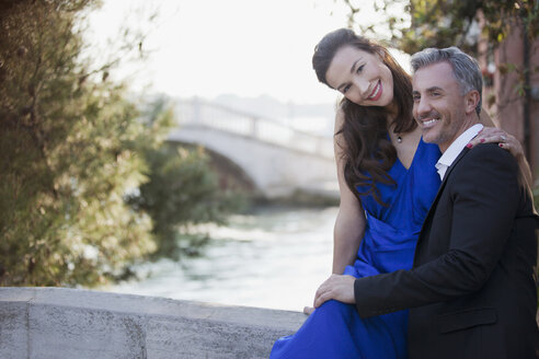 Portrait of smiling well-dressed couple at waterfront - CAIF00498