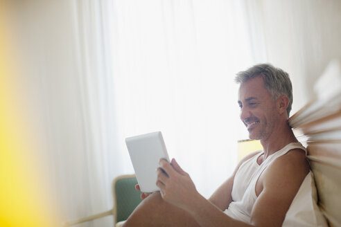Smiling man using digital tablet in bed - CAIF00507