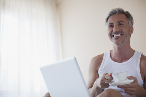 Smiling man drinking coffee and using laptop in bedroom - CAIF00519