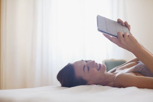 Smiling woman laying on bed and using digital tablet - CAIF00525