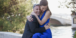 Happy well-dressed couple hugging - CAIF00534