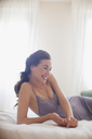 Smiling woman laying in bed - CAIF00549