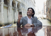 Smiling businessman holding cell phone and leaning on boat in canal in Venice - CAIF00561
