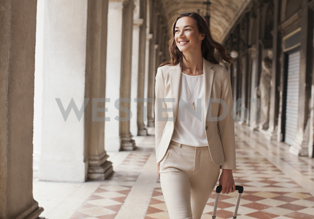 Confident businesswoman pulling suitcase along corridor - CAIF00567