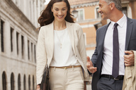 Smiling businessman and businesswoman walking - CAIF00573
