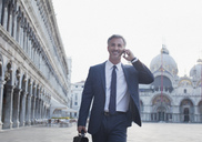 Smiling businessman talking on cell phone and walking through St. Mark's Square in Venice - CAIF00576