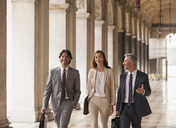 Smiling business people walking along corridor - CAIF00579