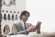 Businessman using digital tablet at sidewalk cafe in Venice - CAIF00588
