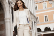 Portrait of smiling businesswoman walking - CAIF00591