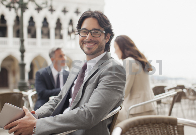 Portrait of smiling businessman holding digital tablet at sidewalk cafe in Venice - CAIF00600