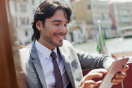 Smiling businessman using digital tablet on boat in Venice - CAIF00615