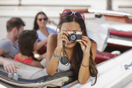 Woman taking picture from convertible - CAIF00660